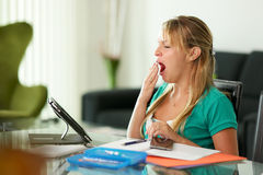 Young woman female student yawning while studying Royalty Free Stock Images