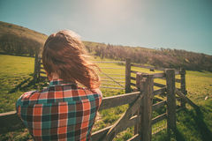 Young woman by a fence on a ranch. Young woman is standing by a fence on a ranch with cattle in the distance royalty free stock image