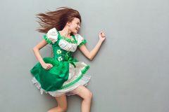 Young woman in a festive dress saint patrick`s day top view running away stock image