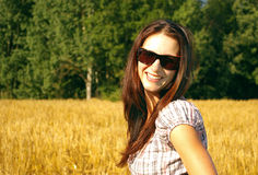 Young woman in the field. Young beautiful laughing woman in the  rye field Royalty Free Stock Photo