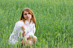 Young woman sitting in a grass Stock Images