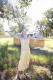 Young woman in field with arms outstretched by camper van, eyes closed (lens flare). Young women in field with arms outstretched by camper van, eyes closed (lens stock image