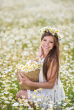 Young woman in a field of blooming daisies Stock Images