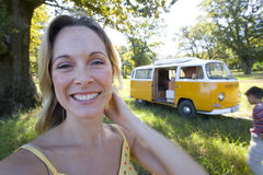 Young woman in field by camper van, smiling, portrait, close-up Royalty Free Stock Image