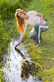 Young woman in Field at creek Royalty Free Stock Images