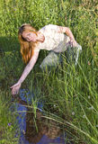 Young woman in Field at creek Stock Images