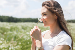 Young woman with a field with daisies Royalty Free Stock Photo