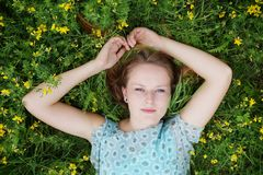 Young woman in a field of flowers. Young woman lying in a flower meadow enjoying sweet idleness Stock Photo