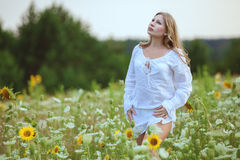 Young woman in field flowers. Royalty Free Stock Photo
