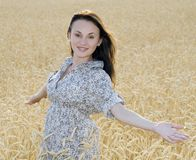 Woman in the field of golden wheat stock image