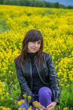 Young woman on the field. Young woman sitting on the blossom mustard field. Full of yellow flowers Stock Image
