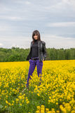 Young woman on the field. Young woman staying, smiling on the blossom mustard field. Full of yellow flowers. Hands in pants pockets Stock Images