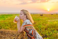 A young woman in a field at sunset happily drinks beer from a glass beer mug, leaning on a straw briquette. Awesome vacation mood. Warm summer evening royalty free stock photo
