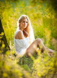 Young woman on field in white dress Stock Images