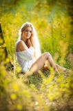 Young woman on field in white dress Royalty Free Stock Images