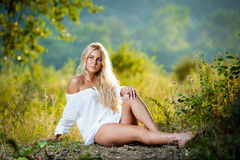 Young woman on field in white dress Stock Photos