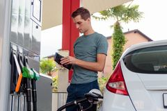 Young handsome man checking his wallet during gasoline refilling. Young woman filling car with gasoline. check balance at the gas pump royalty free stock photos