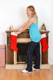 Young woman filling christmas stocking Royalty Free Stock Image
