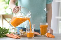 Young woman filling glass of fresh carrot juice. In the kitchen stock image