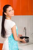 Young woman filling stewpan with water Stock Image