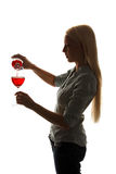 Young woman fills out a glass of red wine Royalty Free Stock Photos