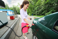 Young woman fills petrol car Stock Photos