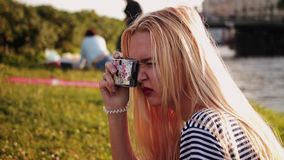 Young woman with a film camera taking pictures and laughs stock video