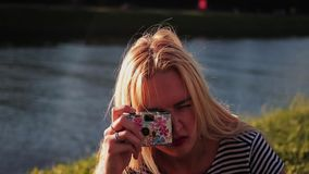 Young woman with a film camera taking pictures and laughs stock footage