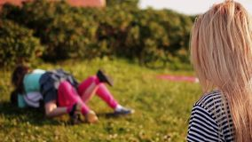 Young woman with a film camera taking pictures and laughs two childrens on background stock video footage