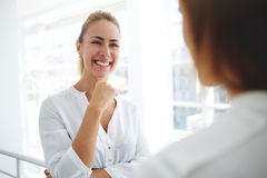 young woman financier with beautiful smile listening her colleague while standing in modern office interior Royalty Free Stock Image