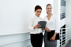 Young woman financier consulting with managing director about own work on digital tablet while standing in modern office interior, royalty free stock photography
