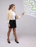 Young woman finding the maze solution, writing on whiteboard. Young businesswoman finding the maze solution writing on whiteboard stock photos