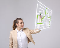 Young woman finding the maze solution, writing on whiteboard. Young businesswoman finding the maze solution writing on whiteboard royalty free stock photography