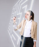 Young woman finding the maze solution, writing on whiteboard. Royalty Free Stock Images