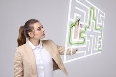 Young woman finding the maze solution, writing on whiteboard. Young businesswoman finding the maze solution writing on whiteboard royalty free stock image