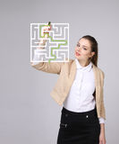 Young woman finding the maze solution, writing on whiteboard. Young businesswoman finding the maze solution writing on whiteboard royalty free stock images