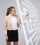 Young woman finding the maze solution, writing on whiteboard. Young businesswoman finding the maze solution writing on whiteboard royalty free stock photo