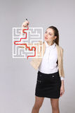 Young woman finding the maze solution, writing on whiteboard. Young businesswoman finding the maze solution writing on whiteboard stock photo