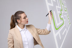 Young woman finding the maze solution, writing on whiteboard. Young businesswoman finding the maze solution writing on whiteboard royalty free stock photos