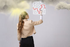 Young woman finding the maze solution, writing on whiteboard. Young businesswoman finding the maze solution writing on whiteboard stock image