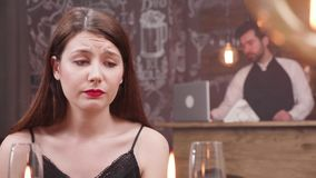 Young woman finds out bad news at a dinner table. Unhappy girl gets very sad at a romantic date in a restaurant stock footage