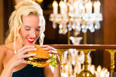 Young woman in fine restaurant, she eats a burger Royalty Free Stock Images
