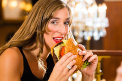 Young woman in fine restaurant, she eats a burger Royalty Free Stock Photos