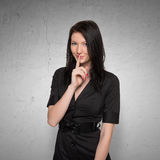 Young woman with finger on her lips gesturing for Royalty Free Stock Photo