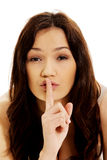 Young woman with finger on lips. Royalty Free Stock Photography