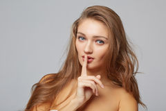 Young woman with finger on lips, on gray background Royalty Free Stock Photography