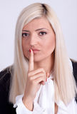Young woman with finger on lips over white background Stock Images