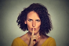Young woman with finger on lips quiet gesture Royalty Free Stock Images