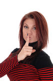 Young woman with finger over mouths. A pretty woman in a red and black striped dress holding her finger over Stock Photography