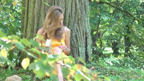 Young woman finished reading book under thick tree trunk. 4K. Young woman finished reading book in the park under thick tree trunk at summertime. 4K UHD video stock video